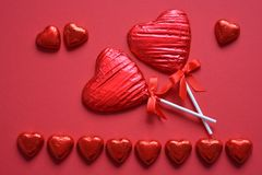 Heart shaped chocolates on red background stock image