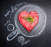 Heart shaped chop of meat on black chalkboard with  painted pan and ingredients, top view Stock Photos