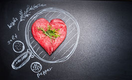 Heart shaped chop of meat on black chalkboard with  painted pan and ingredients, top view, place for text. Stock Photo