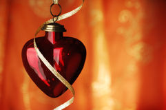 Heart Shaped Christmas Bauble And Ribbon Infront Of Orange Backg. Round, copyspace, selective focus Stock Photography