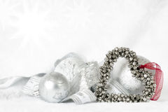 Heart Shaped Christmas Bells over white. Heart-shaped Christmas bells over white, with baubles and ribbon on white fur Royalty Free Stock Photo