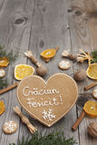 Heart shaped Christmas gingerbread. Heart shaped gingerbread on wooden background, decorated with white icing and with Merry Christmas written in Romanian Royalty Free Stock Photo