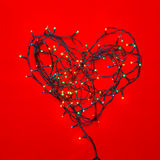 Heart shaped Christmas lights on red Stock Image