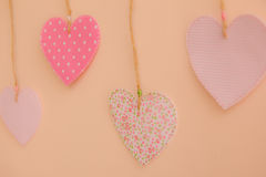 Heart-shaped cloth patches hanging on the wall.  Stock Photos