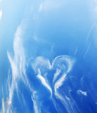 Heart shaped cloud on blue sunny sky. Royalty Free Stock Images