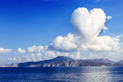 Heart shaped clouds over island Stock Photos