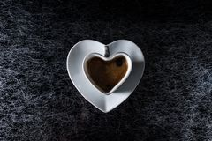 A heart shaped coffe cup with black coffee on a black and silver background kitchen table top Royalty Free Stock Photos