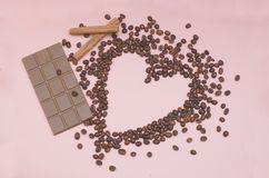 Heart Shaped Coffee Beans and Chocolate Bar onPink Background with Cinnamon Sticks Royalty Free Stock Photography