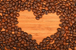 Heart shaped coffee beans frame over bamboo wood background Stock Photo
