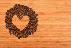 Heart shaped coffee beans frame over bamboo wood background Stock Photography