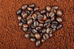 HEART SHAPED COFFEE BEANS ON INSTANT COFFEE BACKGROUND Stock Image