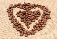 Heart shaped coffee beans on jute background Stock Photo