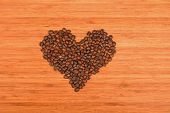 Heart shaped coffee beans over bamboo wood background Stock Images