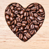 Heart shaped coffee beans on wooden board Royalty Free Stock Images