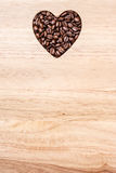 Heart shaped coffee beans on wooden board Stock Photos