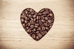 Heart shaped coffee beans on wooden board Royalty Free Stock Photography