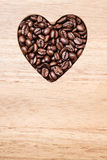 Heart shaped coffee beans on wooden board Stock Image