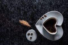 A heart shaped coffee cup with coffee beans, spilled milk and brown sugar on a black background with silver lining Royalty Free Stock Photos