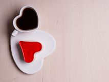Heart shaped coffee cup and cake on wood surface. Heart shaped coffee cup and jelly cake on wooden surface, top view copy space for text Royalty Free Stock Photo
