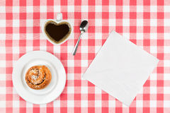 Heart shaped coffee cup and a cinnamon roll Stock Photos