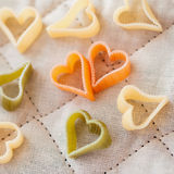 Heart-shaped colored Italian pasta from durum wheat with vegetables on the kitchen textiles, background for Valentine. Heart shaped noodles for Valentine`s Day Royalty Free Stock Photos