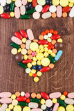 Heart shaped colorful medical pills and capsules, health care concept. Heart shaped colorful medical pills, capsules or supplements for therapy, concept of stock photography