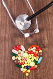 Heart shaped colorful medical pills and capsules with stethoscope, health care concept Royalty Free Stock Photos