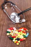 Heart shaped colorful medical pills and capsules with stethoscope, health care concept. Heart shaped colorful medical pills, capsules or supplements for therapy Royalty Free Stock Images