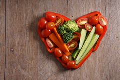 Heart shaped colorful vegetable on wooden background Royalty Free Stock Photo