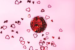 Heart-shaped confetti on pink background stock photography