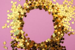 Heart-shaped confetti scattered on a pink background. Celebration and party, concept. Copy space royalty free stock photography