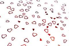 Heart-shaped confetti on white background royalty free stock photo
