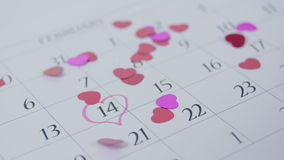 Heart shaped confettis falling on calendar at 14th February stock video