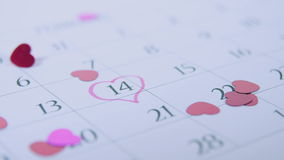 Heart shaped confettis falling on a calendar at 14th February stock footage