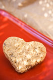 Heart shaped cookie. Heart shaped oatmeal raisin cookie on bright red plate stock photography