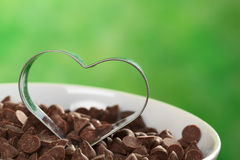Heart-Shaped Cookie Cutter. On chocolate chips (Selective Focus, Focus on the front of the cookie cutter Royalty Free Stock Images