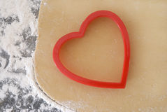 Heart Shaped Cookie Cutter and Dough. Red heart shaped cookie cutter sitting on freshly made cookie dough against a floured granite counter Royalty Free Stock Photo