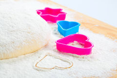 Heart shaped cookie cutter on flour Stock Photos