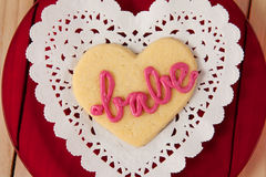 Heart shaped cookie iced with pink cream in text babe on wooden table Stock Photo
