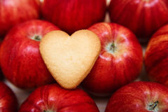 Heart shaped cookie on the red apples Stock Photography