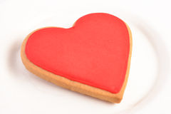Heart shaped cookie. Cookie in a red heart shape on a white porcelain plate Stock Photos
