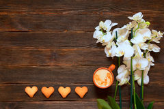 Heart-shaped cookies, cappuccino and orchid on a dark wooden bac. Kground.  Valentine's Day. Concept of care Stock Photos