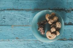 Heart shaped cookies and chocolates on a blue wooden surface. With a place for text, toned Royalty Free Stock Images