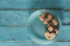 Heart shaped cookies on a blue wooden surface with a place for text, toned. Heart shaped cookies and chocolates on a blue wooden surface with a place for text Stock Photos