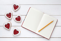 Heart shaped cookies with empty notebook frame and pencil composition for Valentines Day Stock Photo