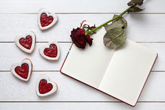 Heart shaped cookies with empty notebook frame and red rose gift composition for Valentines Day Stock Image
