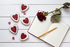 Heart shaped cookies with empty notebook, pencil and red rose gift on white wooden background. Royalty Free Stock Photos