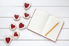 Heart shaped cookies with empty notebook and pencil on white wooden background for Valentines day Stock Image