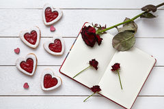 Heart shaped cookies with empty notebook and roses on white wooden background for Valentines day. Stock Images