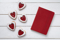 Heart shaped cookies with empty red notebook, composition on white wooden background for Valentines day. Stock Photo